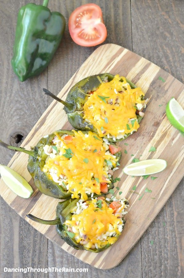 Three Vegetarian Stuffed Poblano Peppers on a wooden cutting board on a wooden table with a raw poblano, half a tomato, and slices of lime