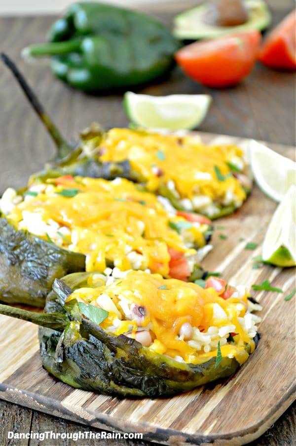 Three Vegetarian Stuffed Peppers on a wooden cutting board with slices of lime, tomato, and a whole poblano pepper
