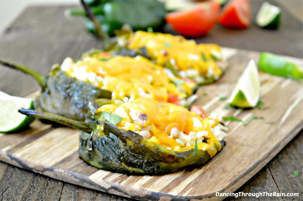 Three Vegetarian Stuffed Poblano Peppers on a wooden cutting board next to more peppers, tomato slices and lime wedges
