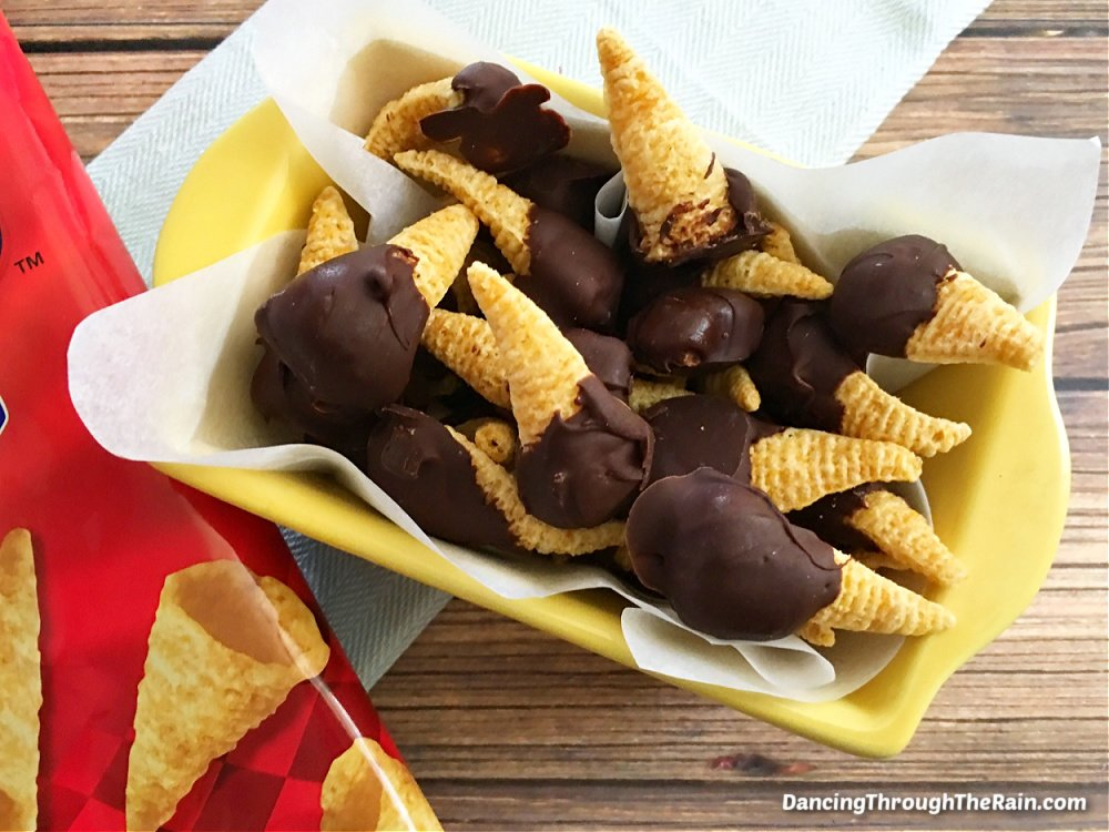 Chocolate Peanut Butter Bugles in a white serving dish next to the red bag of Bugles on a wooden table