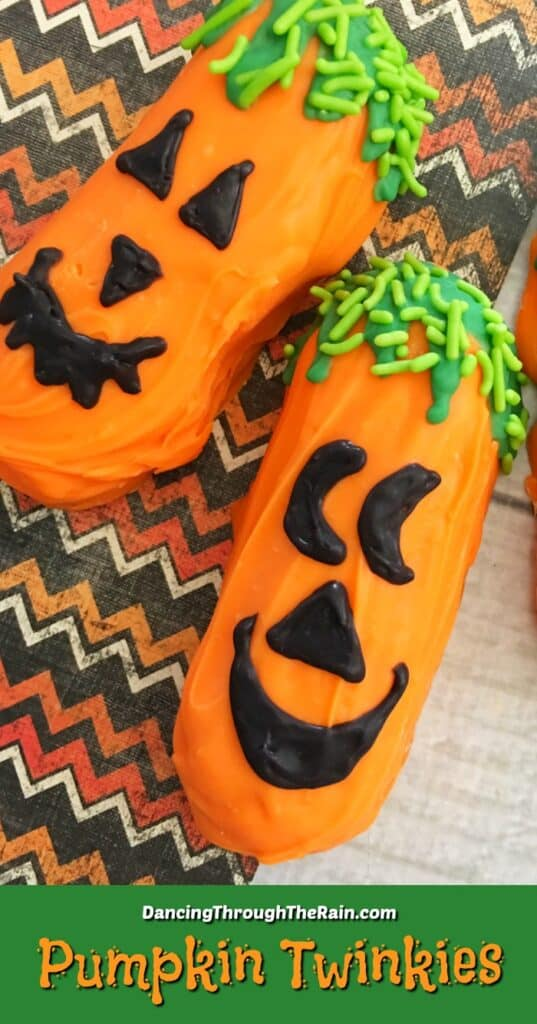 Two Halloween Twinkies Jack O Lanterns on an orange and black zigzag patterned placemat