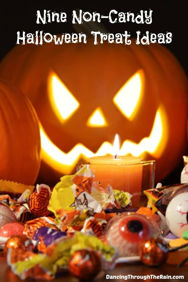 A jack o lantern with candle and candy wrappers around it