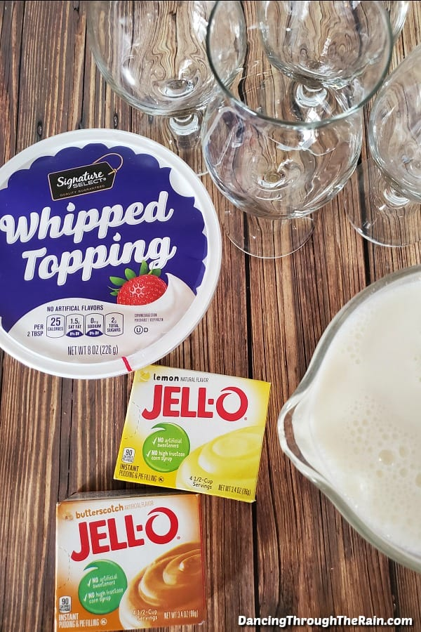 A Whipped Topping tub, four parfait glasses, a box of lemon Jello pudding, a box of butterscotch Jello Pudding and a measuring cup of milk on a wood table