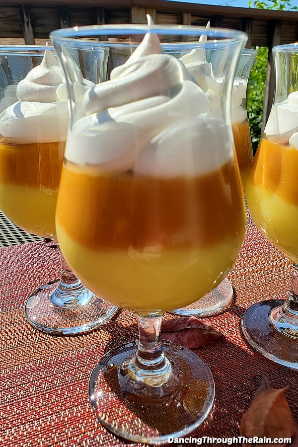 Candy corn pudding parfaits on a red striped placemat