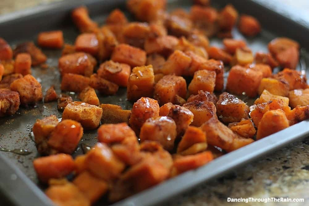 Cubed and seasoned sweet potatoes on a baking sheet with honey drizzled on top