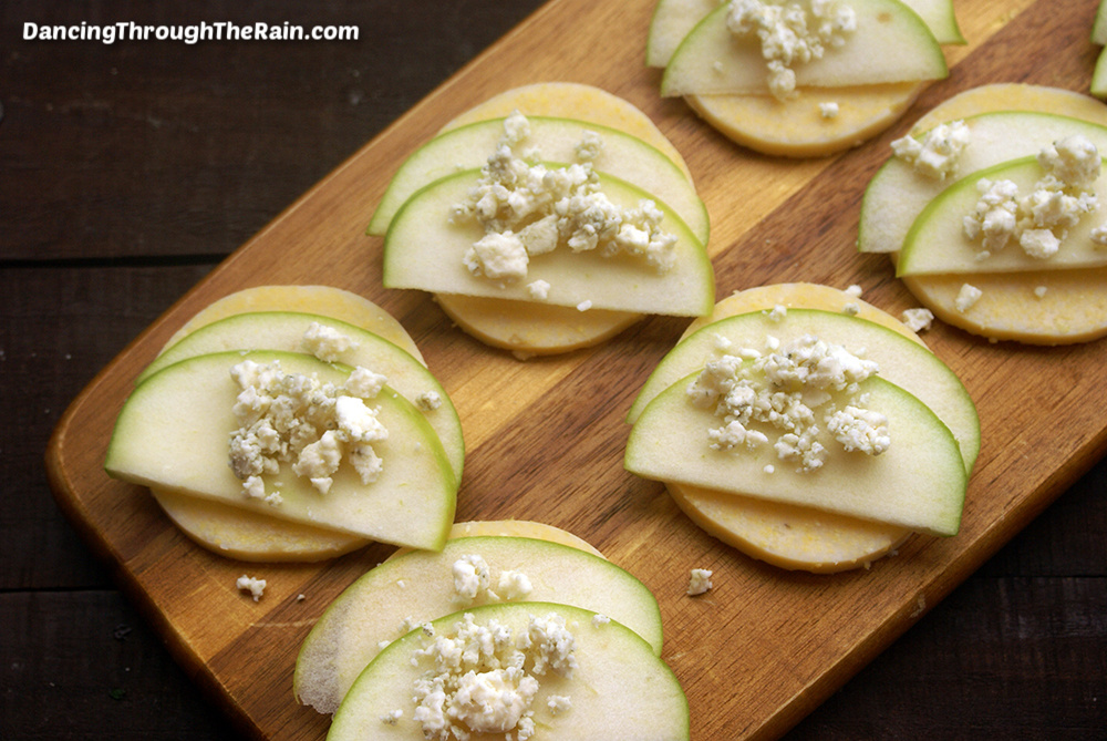 Six Polenta Bites with Apple and Gorgonzola on a wooden cutting board