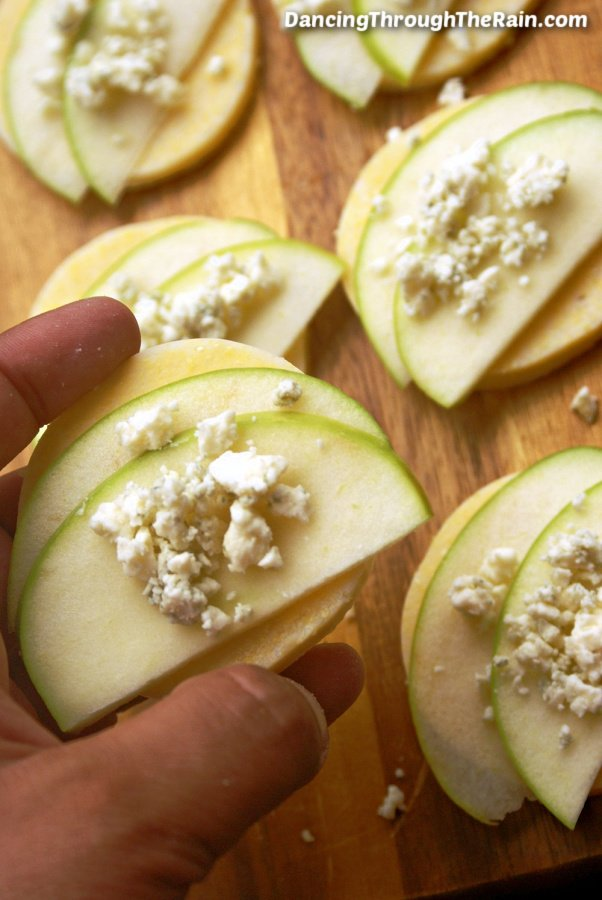 Five Polenta Bites with Apple and Gorgonzola on a wooden cutting board and a hand holding up another one