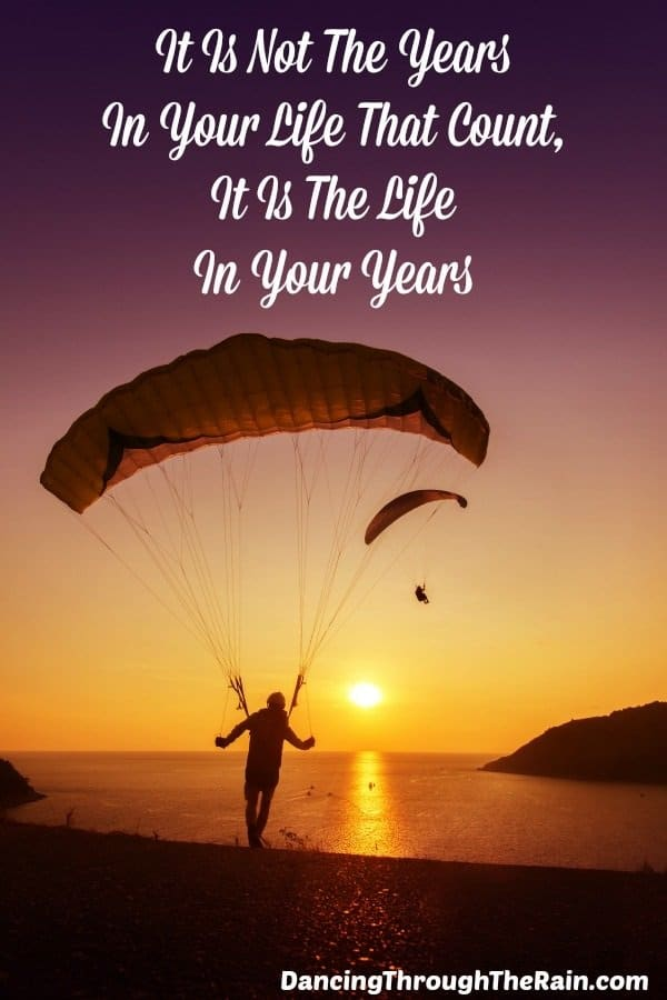 "A person landing on ground with a parachute during sunset with the words ""It is not the years in your life that count, it is the life in your years"" above"