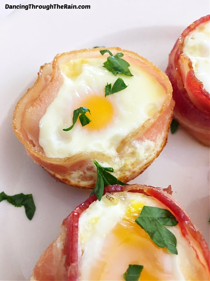 Three Bacon Wrapped Egg Cups on a white plate