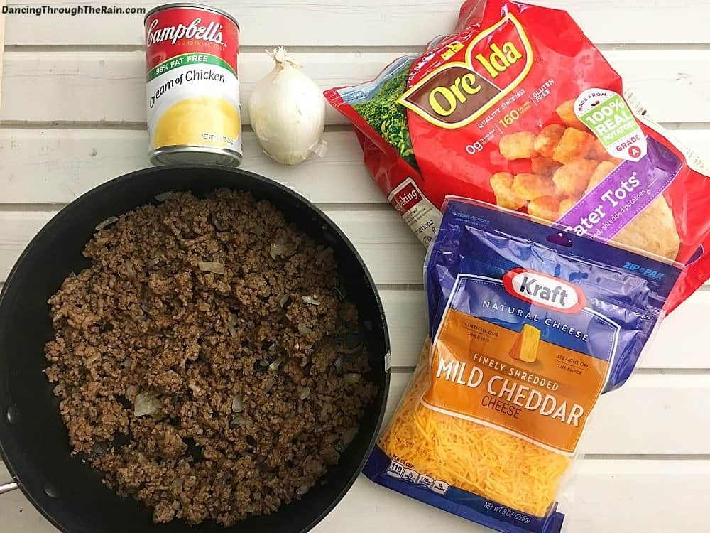 Ground beef in a pan, Cambell's Cream of Chicken Soup can, Ore Ida frozen tater tots, shredded cheddar cheese and an onion on a table