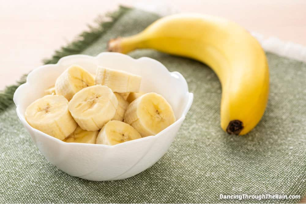 A white bowl of sliced bananas next to another full banana on a green placemat
