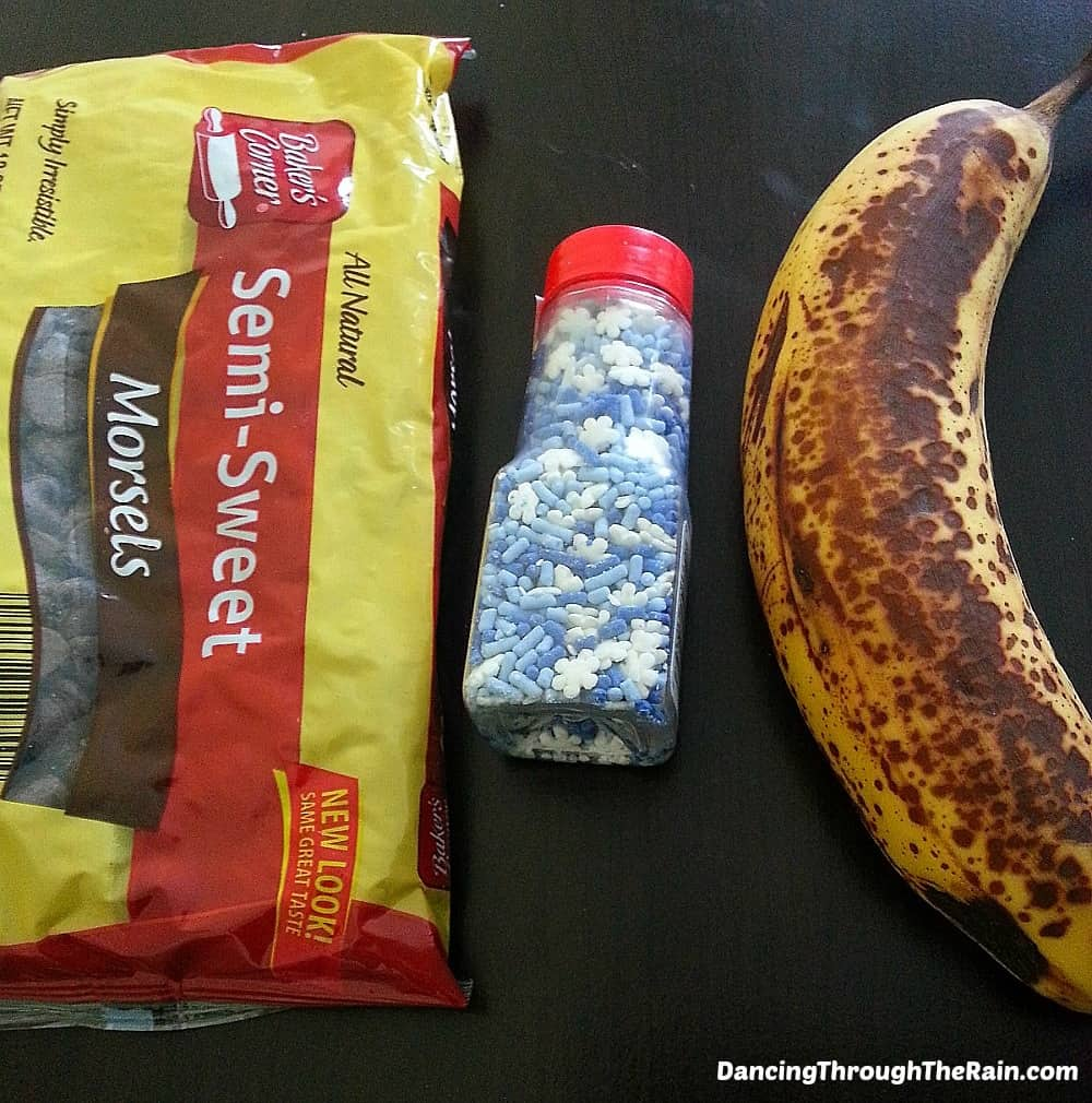 Chocolate chips in a bag, blue and white sprinkles, and a banana on a table
