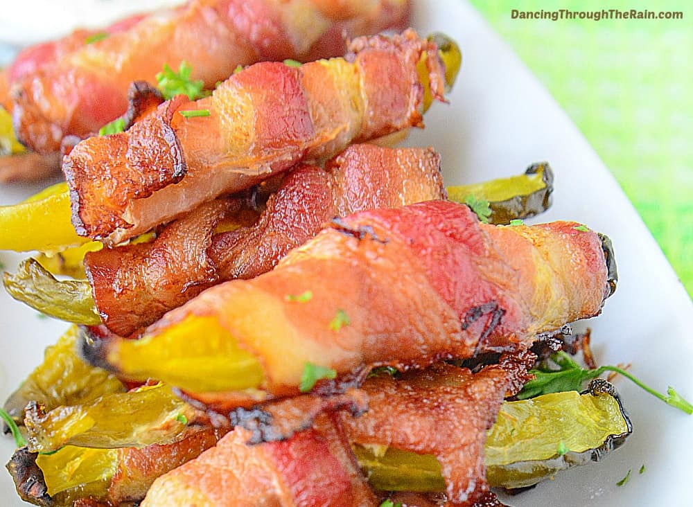 Cooked bacon wrapped pickles on a white plate