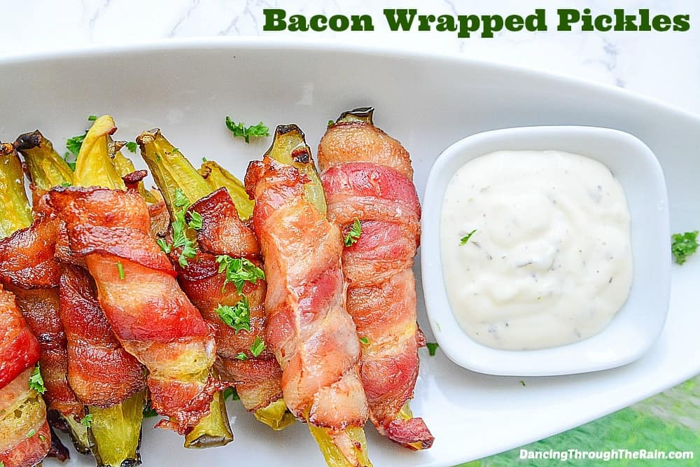 Bacon wrapped pickles on a white plate with ranch dip