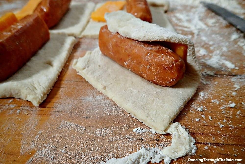 Sausage and Cheese Being Wrapped In Dough