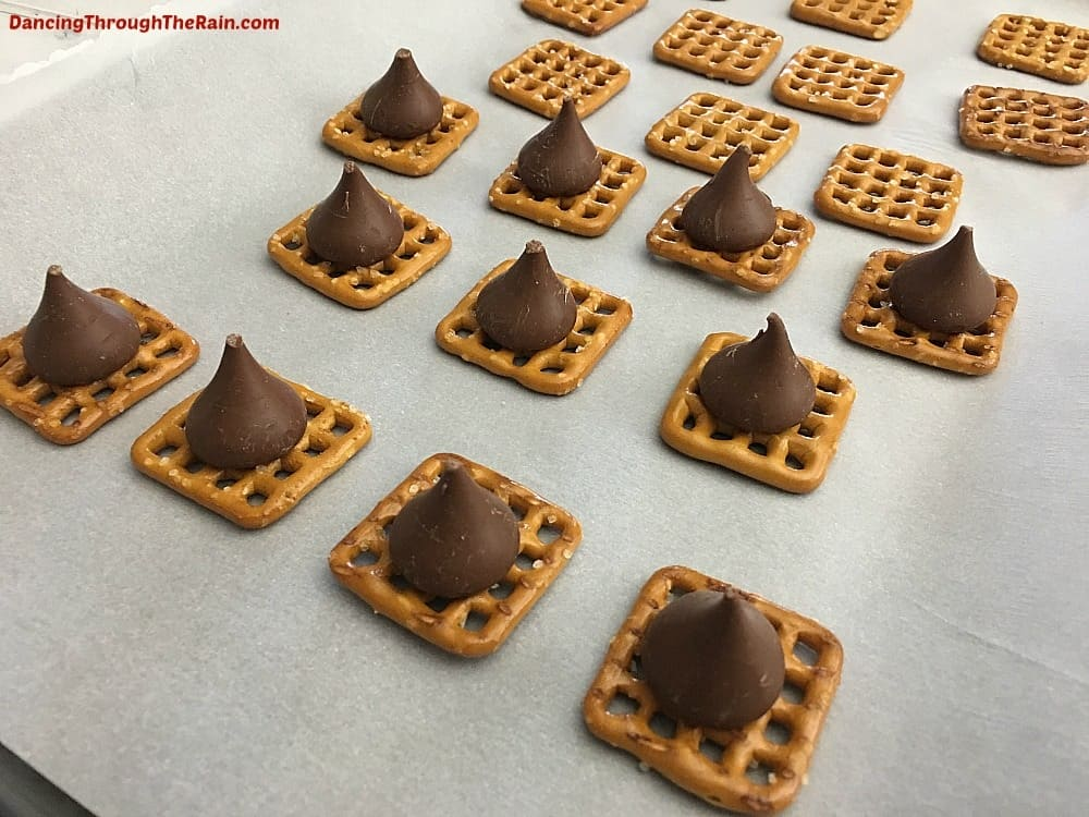 Pretzels on a baking sheet with parchment paper, topped by Hershey's Kisses