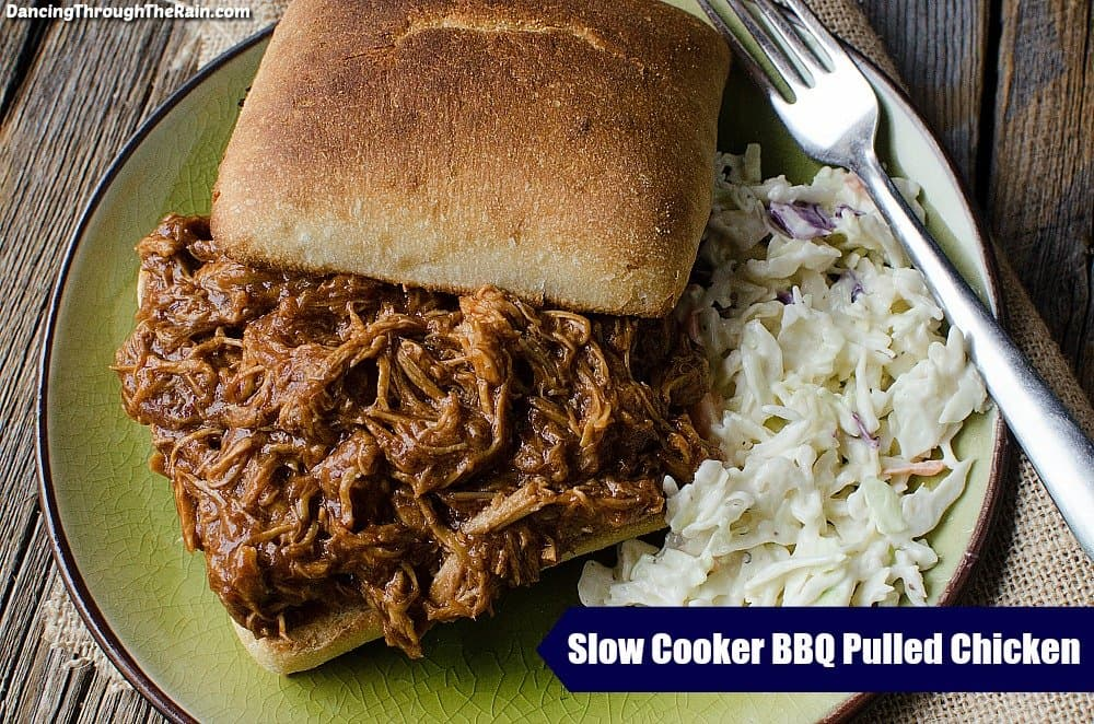 Slow Cooker Pulled Chicken on a bun next to coleslaw on a green plate