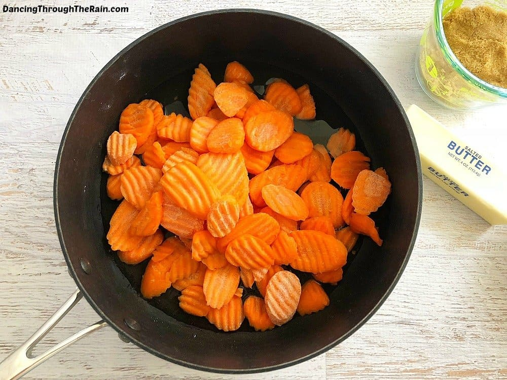 A bunch of frozen wavy carrots in a black pot next to a stick of butter and a container of brown sugar on a white table