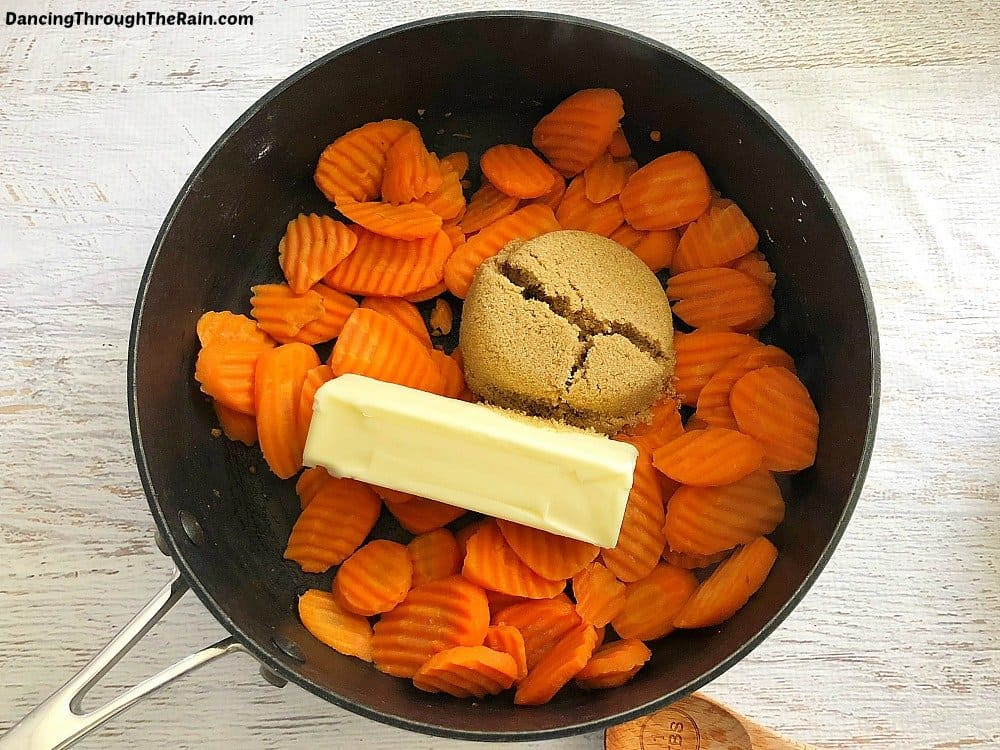 Wavy carrots in a pot with brown sugar and a stick of butter