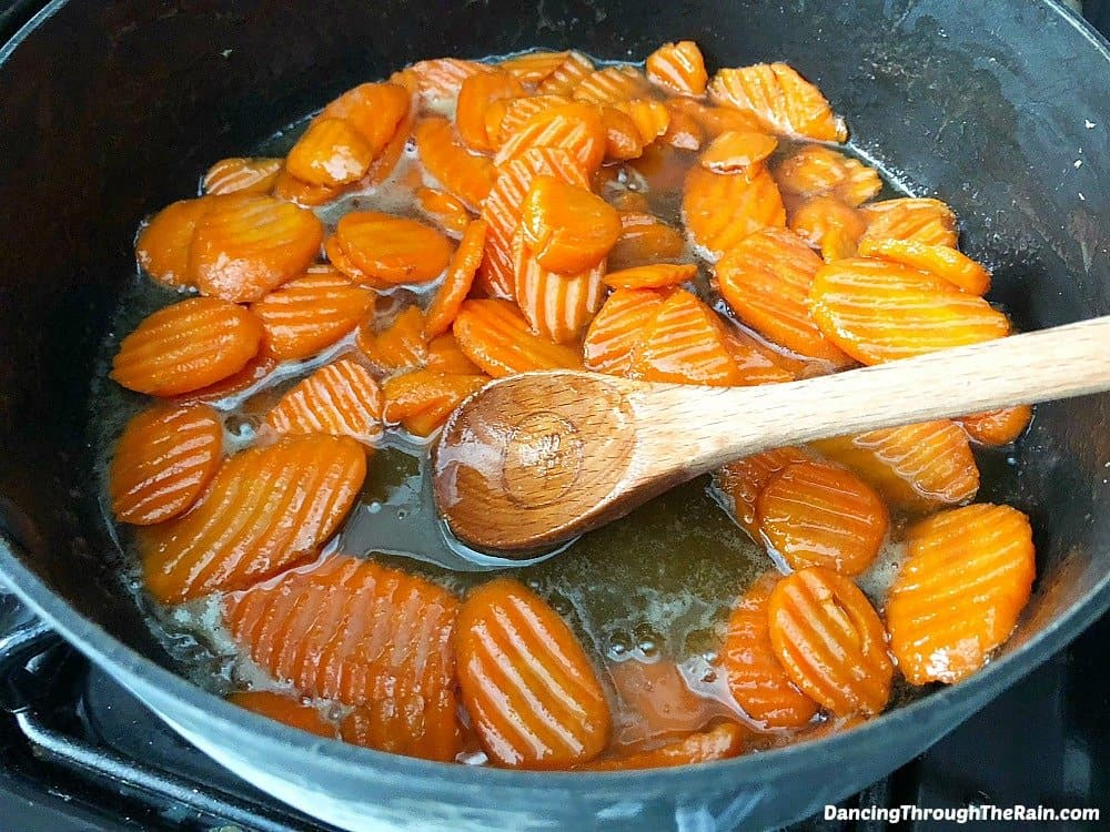 Frozen glazed carrots that are cooking into candied carrots in a large pot with a wooden spoon