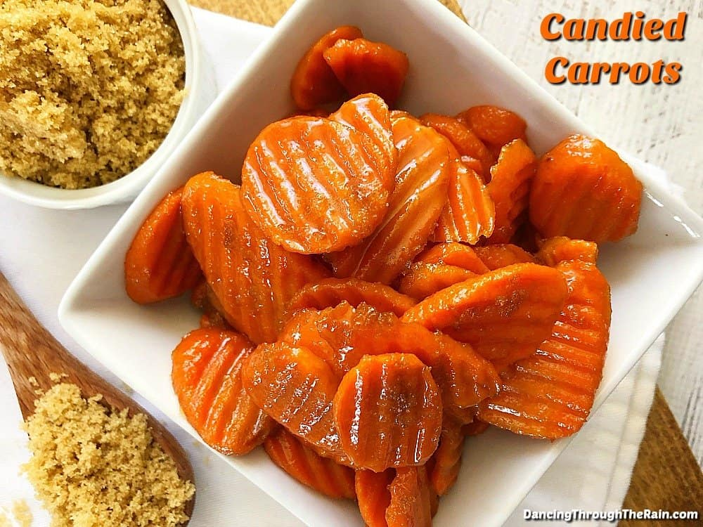 Candied carrots in a white bowl next to brown sugar
