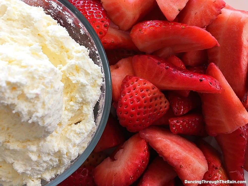 Cheesecake Dip in a clear bowl next to strawberries