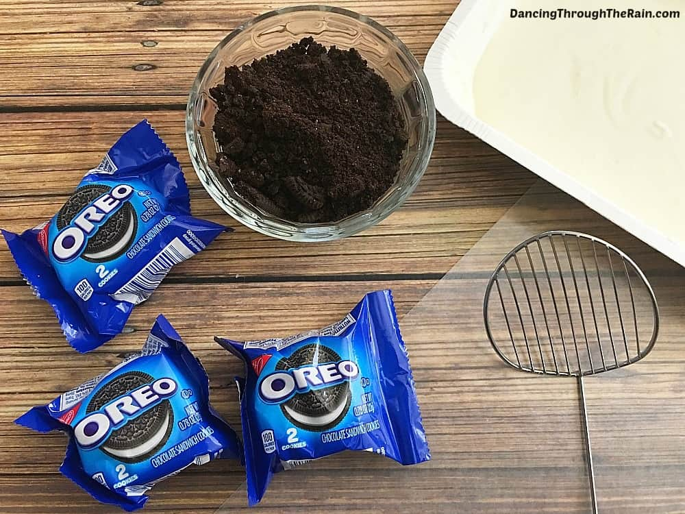 Oreo cookies packets, crushed oreo cookies in a bowl, and a cookie strainer