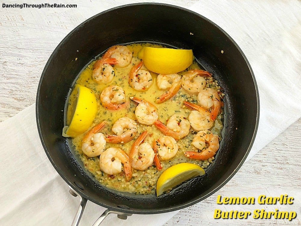 Lemon Garlic Butter Shrimp in a black cooking pan on a white placemat on a wooden table