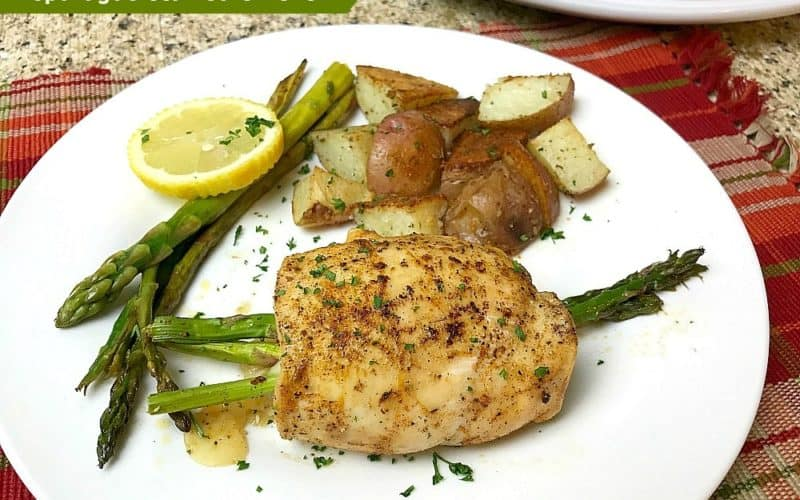 A whole piece of Asparagus Stuffed Chicken with Provolone Cheese on a white plate next to a pile of roasted potatoes, more asparagus pieces and a lemon slice