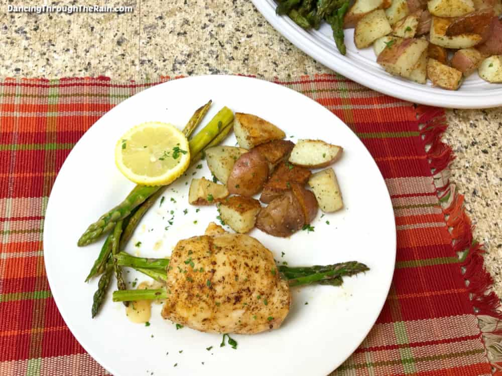 A large piece of Asparagus Stuffed Chicken with Provolone Cheese on a white plate with a pile of cooked potato pieces and more spears of asparagus with a lemon slice on a red checkered placemat