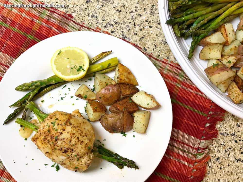 A white plate with a full Provolone Chicken with Asparagus next to roasted potato pieces and more asparagus with a lemon slice next to a white bowl of more cooked potatoes and asparagus