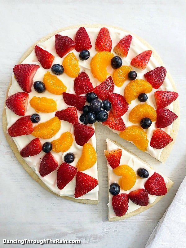 A large sugar cookie fruit pizza with one triangle slice cut out and moved away from the whole