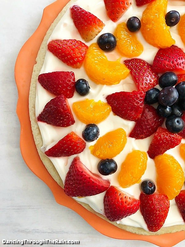 A closeup of half of the best sugar cookie fruit pizza on an orange serving tray