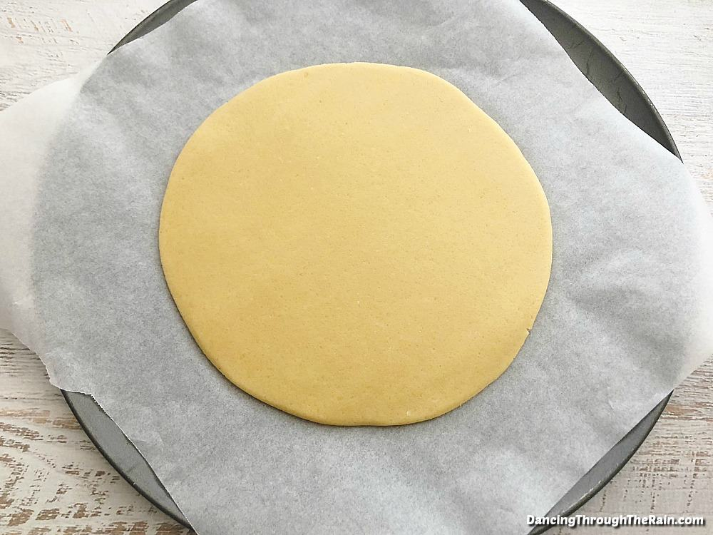 Dough that has been flattened with a rolling pin in a circle on a pizza pan with parchment paper