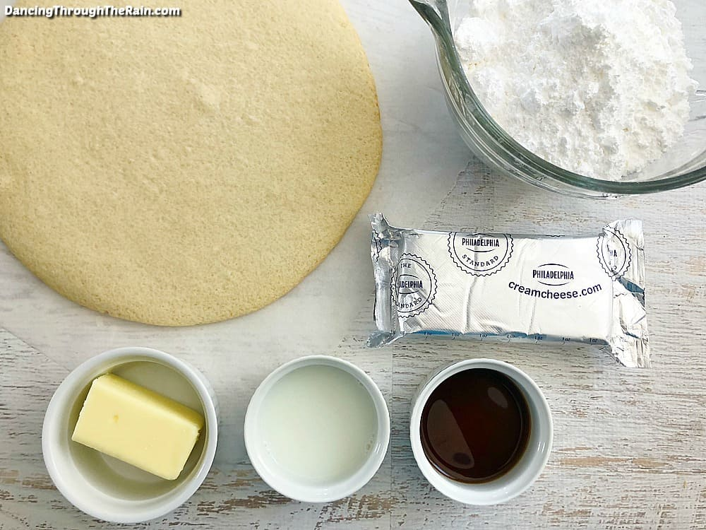 A round baked sugar cookie on a white wooden table next to a clear bowl of sugar, a brick of cream cheese, and three other white bowls with ingredients