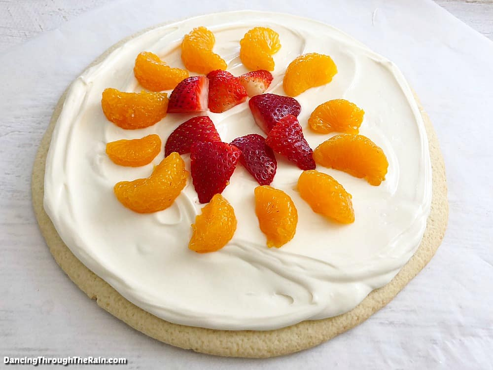 A large sugar cookie with cream cheese frosting spread on top and cut strawberries and mandarin oranges laying on top