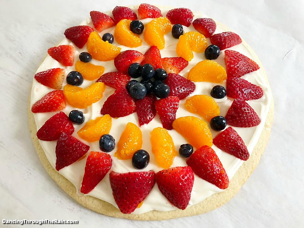 A whole Sugar Cookie Fruit Pizza on a white table with strawberries, blueberries, and mandarin oranges