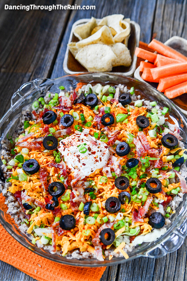 A clear pie plate full of Black Eyed Pea Taco Dip on an orange fabric napkin next to two bowls of corn chips and carrot sticks on a wooden table