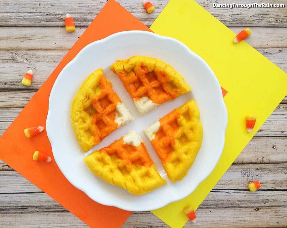 Halloween waffles cut into four pieces on a white plate on top of orange and yellow placemats on a wooden table with candy corn