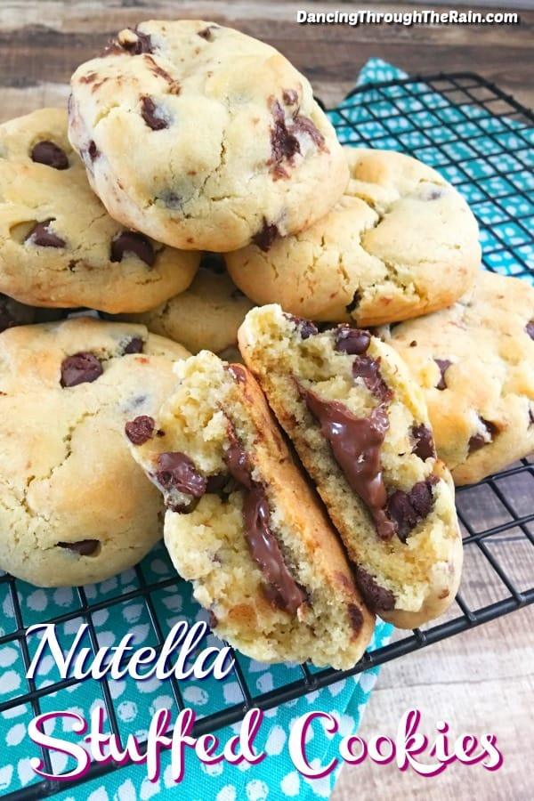Seven Nutella Stuffed Cookies on a black wire rack on top of a blue and white tablecloth with one cookie broken in half to see the Nutella inside