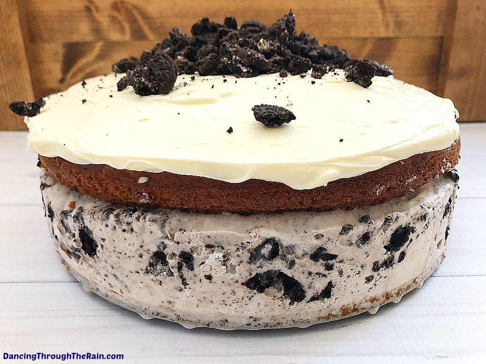 A frosted semi-homemade Oreo Ice Cream Cake on a gray table with crushed Oreo cookies crumbled on top