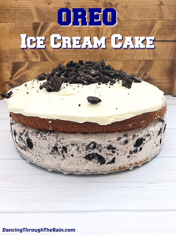 An Oreo Ice Cream Cake on a gray table with crush Oreos cascading off the vanilla frosting on top