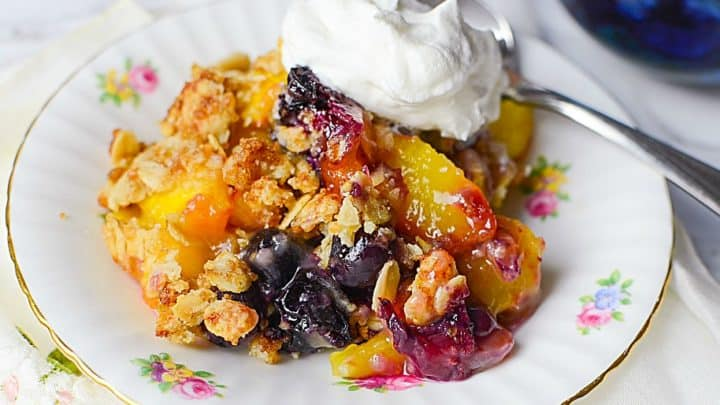 A scoop of Peach Blueberry Crisp on a white plate with a dollop of whipped cream and a metal spoon