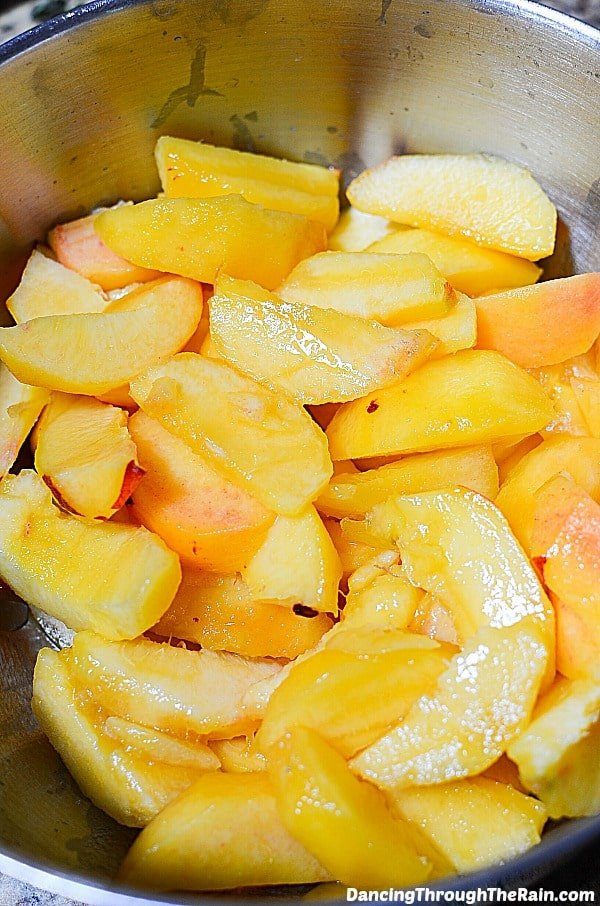 A large metal bowl with fresh peach slices inside
