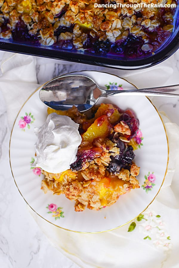 A scoop of Peach Blueberry Crisp on a white plate with a scoop of whipped cream and a metal fork next to the baking dish with the rest of the crisp