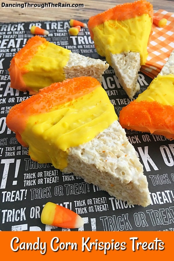 Four Candy Corn Rice Krispie Treats on a black and white Halloween words placemat next to candy corn candy pieces