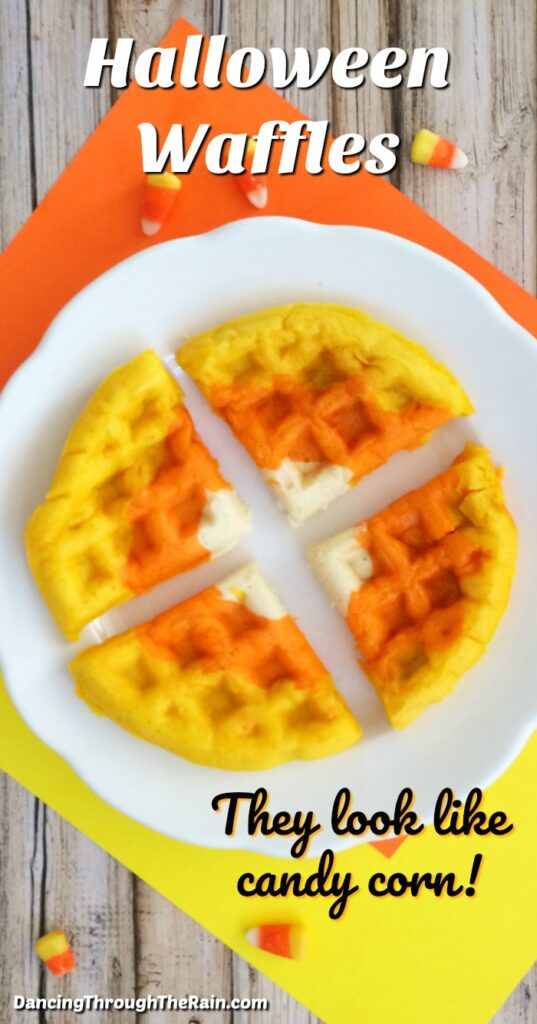 Halloween Waffles that look like candy corn cut into four pieces on a white plate on a yellow and orange placemat on a wooden table