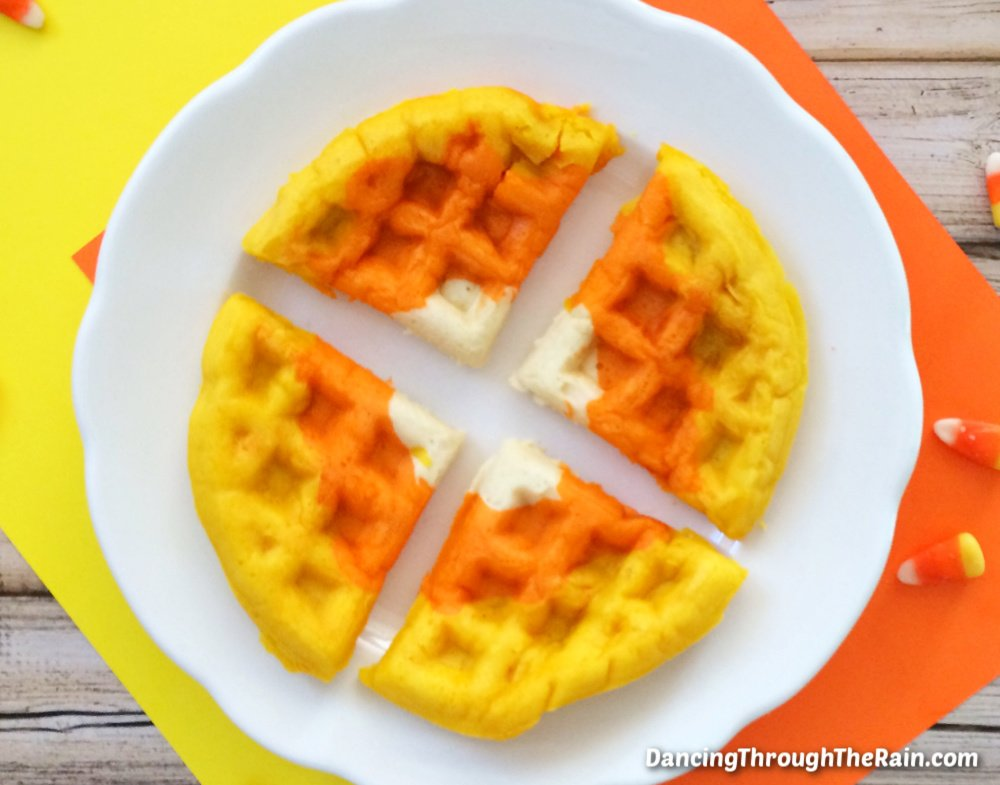 Halloween Waffles that look like candy corn cut in four pieces on a white plate