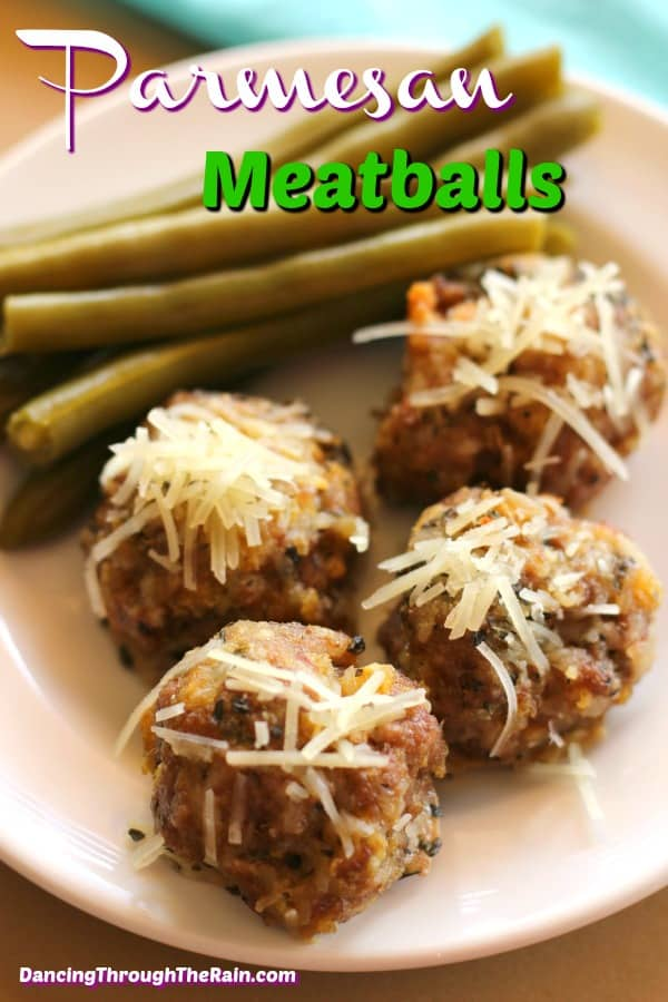 Four parmesan meatballs next to cooked green beans on a white plate