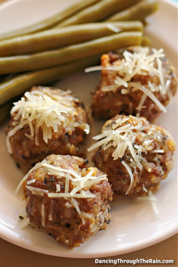 Garlic Parmesan Meatballs on a white plate next to cooked green beans